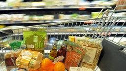 Ein Kunde schiebt einen Einkaufwagen mit unterschiedlichen Bio-Produkten durch einen Bioladen. © dpa Foto: David Ebener