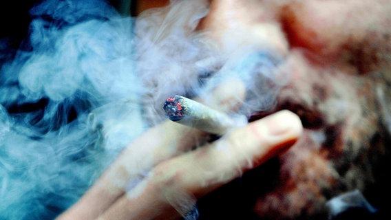 Ein Mann raucht einen Joint. © picture alliance / dpa Foto: Anthony Picore