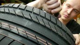 Ein Mann kontrolliert Reifen. © dpa Foto: Rainer Jensen