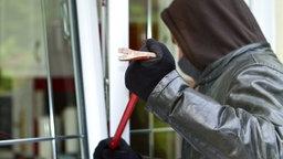 Maskierter Einbrecher bricht ein Fenster auf. © Fotolia.com Foto: sdecoret