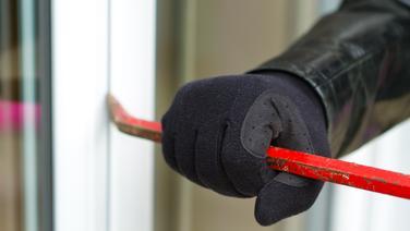Einbrecher hebelt mit einem Brecheisen ein Fenster auf. © Fotolia.com Foto: sdecoret