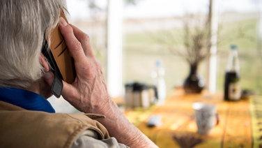 Senior schaut aus dem Fenster während eines Telefonats | picture alliance
