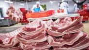 Arbeiter in einem Fleischzerlegebetrieb. Im Vordergrund sind Rippen und Bauchfleisch vom Schwein zu sehen. © dpa picture alliance Foto: Christian Charisius