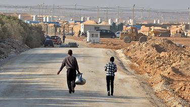 Syrische Flüchtlinge gehen auf einer Straße. Im Hintergrund ein Auffanglager in Jordanien. © dpa picture alliance Foto: Yann Foreix