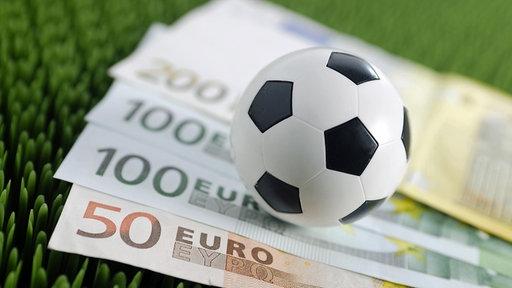 Auf einem Stück Kunstrasen liegen mehrere Geldscheine sowie ein kleiner Fußball.