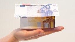 Ein Haus aus Geld auf einer Hand. © picture alliance / dpa Foto: Franziska Koark