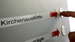 """Ein Schild mit der Aufschrift """"Kirchenaustritte"""" zum Ziehen einer Wartenummer in einer Behörde © picture-alliance/dpa Foto: Oliver Berg"""