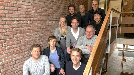 Eine Gruppe von mehreren NDR Journalisten sind auf einer Holztreppe und schaut in die Kamera.