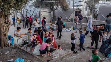 Migranten warten darauf, in einem Zwischenlager neben dem Lager Moria auf der Insel Lesbos Brot zu kaufen. © dpa bildfunk Foto: Angelos Tzortzinis