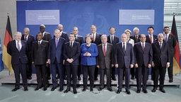 Bundeskanzlerin Merkel steht im Bundeskanzleramt vor der Libyen-Konferenz mit den Teilnehmern für ein Gruppenfoto zusammen. © dpa Foto: Michael Kappeler