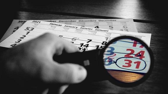 Eine Person hält eine Lupe über ein Kalenderblatt, wo der 31.1.2021 als Lockdown-Ende eingekreist ist. © picture alliance Foto: Fotostand / K. Schmitt