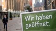 """Auf einem Schild in einer Innenstadt steht """"Wir haben geöffnet"""". © dpa bildfunk Foto: Sina Schuldt"""