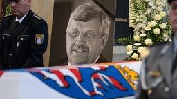 Das Konterfei des getöteten Walter Lübcke ist hinter einem Bundeswehrsoldaten am Sarg bei einem Trauergottesdienst in Kassel zu sehen.