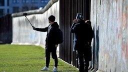Touristen fotografieren sich auf dem Gelände der Gedenkstätte Berliner Mauer an der Bernauer Straße. © dpa bildfunk Foto: Britta Pedersen