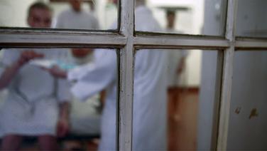 Ein Blick durch ein Fenster, hinter dem ein Mensch Medikamente in einer Psychiatrie einnimmt. | NDR