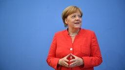 Angela Merkel bei ihrer Sommerpresse-Konferenz, die trägt ein Rotes Jacket. © dpa-Bildfunk Foto: Bernd Von Jutrczenka