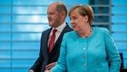 Bundeskanzlerin Angela Merkel (CDU) und Bundesfinanzminister Olaf Scholz (SPD) auf dem Weg zu einer Pressekonferenz im Bundeskanzleramt. © dpa bildfunk Foto: Michael Kappeler