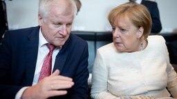 Horst Seehofer und Angela Merkel unterhalten sich bei einer CDU/CSU-Fraktionssitzung. © dpa
