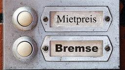 Zwei Klingelschilder an einer Häuserwand. Auf dem oberen steht Mietpreis. Auf dem unteren steht Bremse. © dpa picture alliance Foto: Christian Ohde