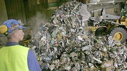 Fabrikarbeiter betrachtet einen Müllberg, der in der Müllverbrennungsanlage Hamburg vorbereitet wird. © dpa Foto: Sebastian Widmann