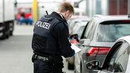Ein Polizeibeamter kontrolliert einen Autofahrer. © dpa bildfunk Foto: Frank Molter