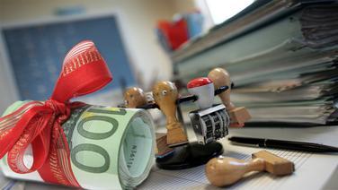 Gerolltes Geldbündel mit Schleife vor einem Behördenschreibtisch (Montage) © picture-alliance/ ZB  --- fotolia Foto: Patrick Pleul --- Joachim Wendler