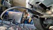 Ein Messschlauch eines Gerätes zur Abgasuntersuchung für Dieselmotoren steckt im Auspuffrohr eines VW Golf TDI. © dpa bildfunk Foto: Patrick Pleul