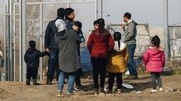 Mehrere syrische Flüchtlinge stehen an einem Grenzzaun zwischen Serbien und Ungarn. © dpa picture alliance Foto: Krystian Maj