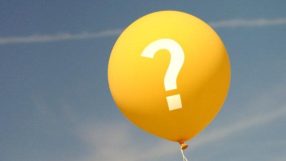 Ein gelber Luftballon mit einem Fragezeichen vor blauem Himmel. © berliner7 Foto: berliner7