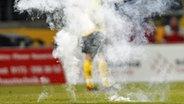 Eine Rauchbombe auf dem Rasen eines Fußballstadions. © dpa Foto: Thomas Eisenhuth