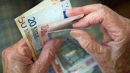 Zwei Hände eines älteren Menschen halten mehrere Geldscheine fest. © dpa picture alliance Foto: Marijan Murat