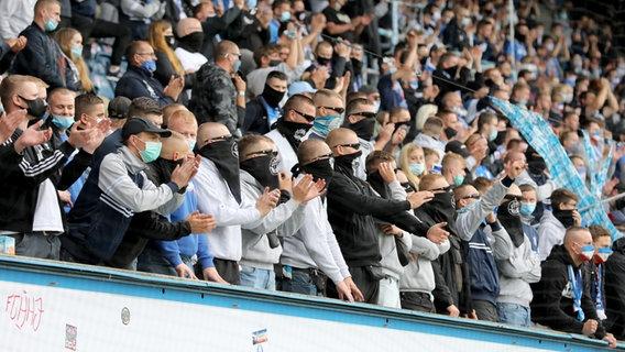 Fans de Hansa sur la tribune sud à Rostock avec protection de la bouche et du nez © photo alliance Photo: Bernd Wüstneck / dpa