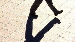 Schatten eines gehenden Mannes © picture-alliance / scanpix Foto: Gunnar Smoliansky