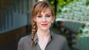 Moderatorin Eva Schulz steht vor einem unscharfen Hintergrund und lächelt in die Kamera. © NN