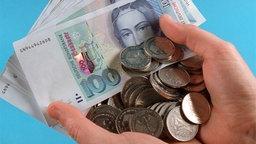 Mehrere 100 D-Mark-Scheine und weitere Münzen liegen in zwei Händen. © dpa / picture-alliance