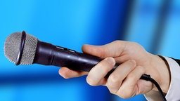 Eine Hand hält ein Mikrofon (Montage). © rolphoto Foto: rolphoto