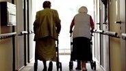 Zwei Senioren gehen mit Rollatoren durch einen Flur. © dpa Foto: Oliver Berg