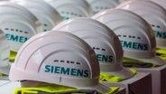 """aufgereihte weiße Schutzhelme mit der Aufschrift """"Siemens"""", darunter jeweils eine gefaltete gelbe Warnweste © dpa Bildfunk Foto: Jens Büttner"""