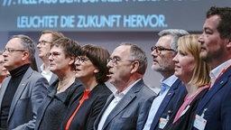 Norbert Walter-Borjans und Saskia Esken (M.) stehen in einer Reihe mit anderen SPD-Politikern beim Parteitag in Berlin. © dpa bildfunk Foto: Michael Kappeler