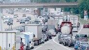 Fahrzeugkolonnen schieben sich über die Autobahn A7 bei Mellendorf in Richtung Norden. © dpa-Bildfunk Foto: Peter Steffen/dpa