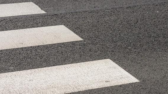 Ein Stück eines auf den Asphalt einer Straße gemalten Zebrastreifens. © dpa picture alliance Foto: SPA