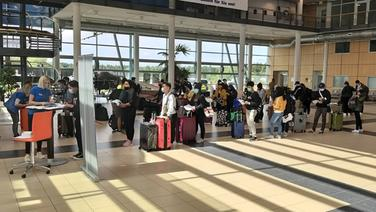 Mehrere AIDA-Mitarbeiter warten bei ihrer Ankunft am Flughafen Rostock Laage in einer Schlange. © NDR Foto: Steffen Baxalary