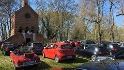 Besetzte Autos stehen vor einer Kirche, Pastor predigt vor dem Eingang der Kirche. Foto: Christopher Niemann