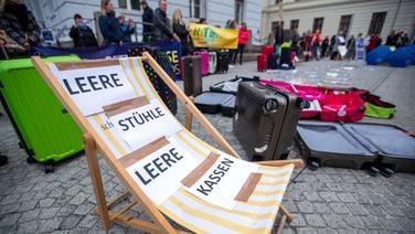 Mit leeren Liegestühlen demonstrieren Mitarbeiter von Reisebüros und Tourismusbetrieben vor der Staatskanzlei für eine Exitstrategie aus der Corona-Krise. © dpa-Bildfunk Foto: Jens Büttner