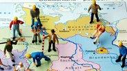 Kleine Plastikfiguren stehen auf einer Landkarte von Deutschland verteilt auf die Bundesländer - gerade ein Drittel der Figuren stehen auf der ostdeutschen Kartenseite (Illustrationsfoto vom 07.11.2005). © dpa Foto: Jens Büttner