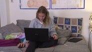 Eine Studentin sitzt mit einem Laptop auf einem Sofa. © NDR Foto: Screenshot
