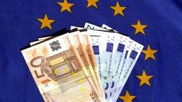 Ein Bündel Euroscheine liegt auf dem EU-Logo. © imago/eyevisto