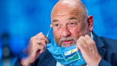 MV-Wirtschaftsminister Harry Glawe (CDU) legt während einer PK einen Mund-Nasenschutz ab. | dpa/picture-alliance