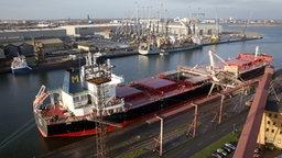 Im Seehafen Rostock wird am 07.01.2014 der Massengutfrachter Clia mit Weizen beladen, im Hintergrund das Kranwerk von Liebherr. © dpa-Zentralbild Fotograf: Bernd Wüstneck