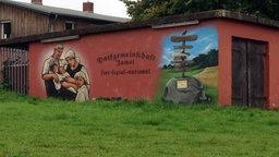 """Ein Gebäude im nordwestmecklenburgischen Jamel ist mit den Worten """"Dorfgemeinschaft Jamel: frei, national, sozial"""" und Bildern bemalt. © ndr.de Foto: Silke Hasselmann"""